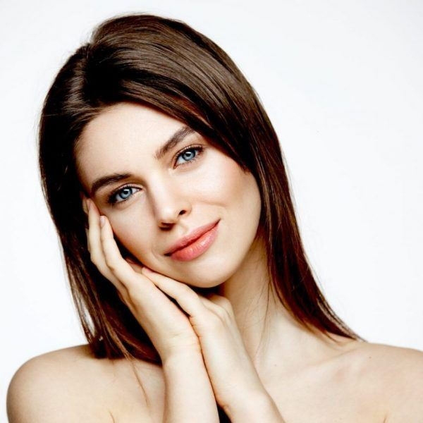Naked young beautiful girl with natural make up smiling looking at camera over white background. Cosmetology and spa. Facial treatment. Copy space.