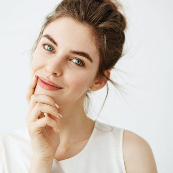 Portrait of young beautiful tender girl with bun smiling looking at camera touching face over white background.  Copy space.