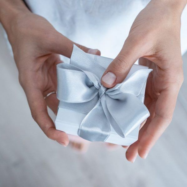Woman hands holding Gift box, close-up. Wide angle format backdrop