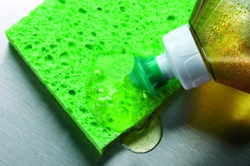 macro shot of dish soap being squeezed onto green sponge in aluminum sink